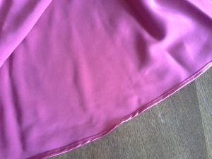 Wrong side of rolled hem on red silk satin