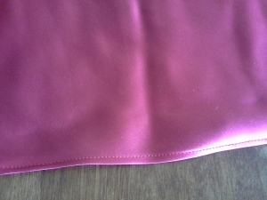 Right side of rolled hem on red silk
